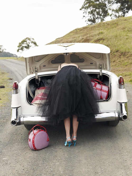 Woman in tutu, looking in trunk